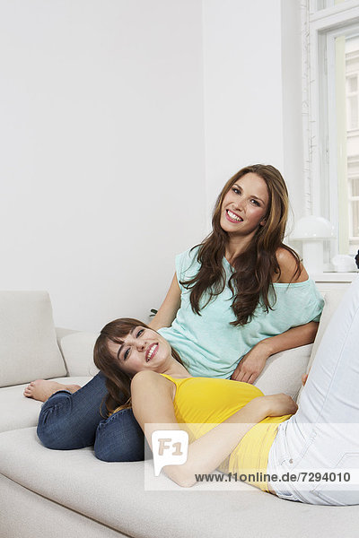 Young women sitting on couch  smiling  portrait