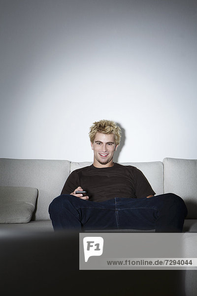 Young man sitting on couch in front of screen