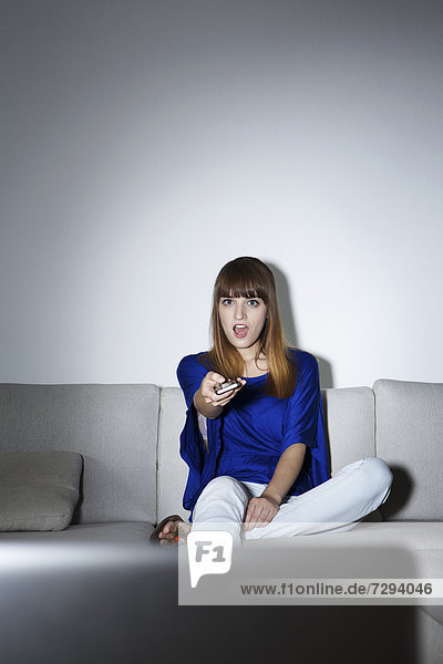 Junge Frau auf der Couch vor dem Bildschirm sitzend