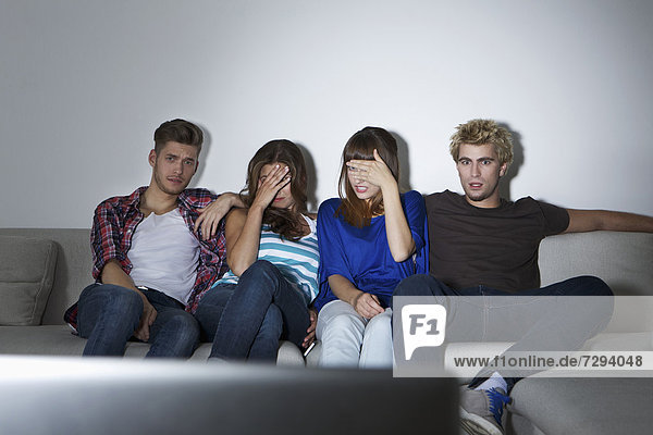 Germany  Berlin  Group of young people sitting on couch in front of screen