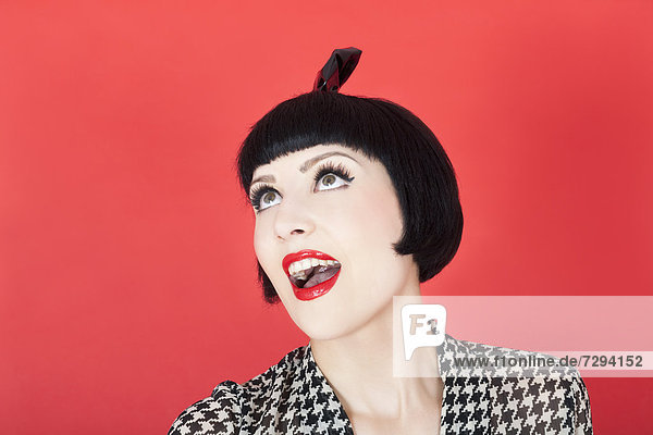 Close up of young woman against red background