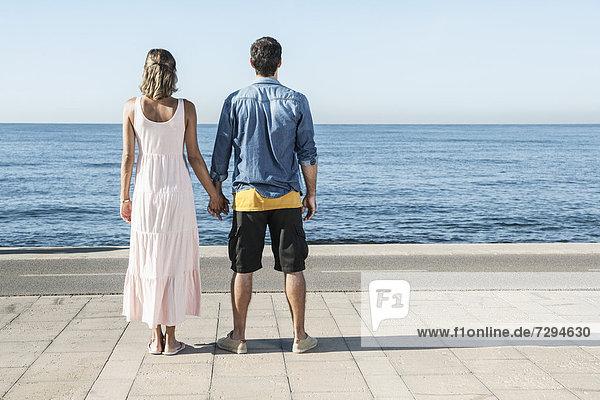 Spanien  Mittleres erwachsenes Paar am Atlantik stehend  mit Blick auf den Atlantik