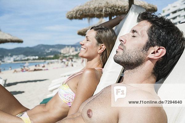 Spanien  Mittleres erwachsenes Paar entspannt auf Strandkorb