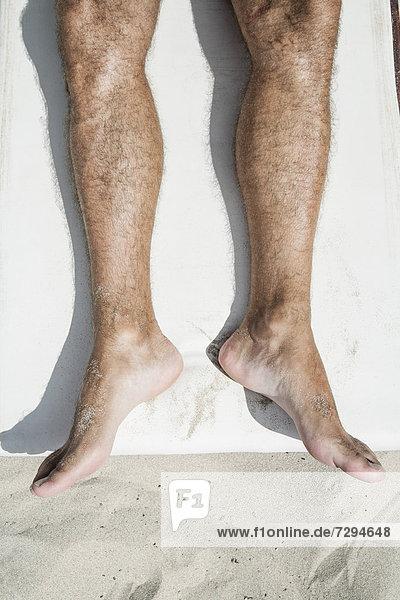 Spain  Human legs on beach towel