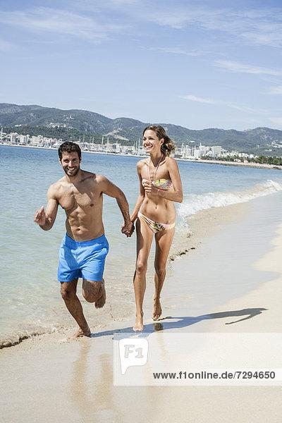 Spain  Mid adult couple running on beach
