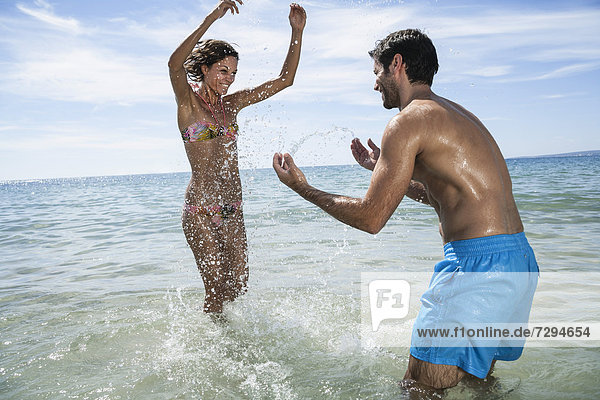 Spain  Mid adult couple playing in beach