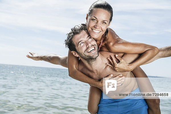 Spain  Mid adult man giving piggy back ride to woman