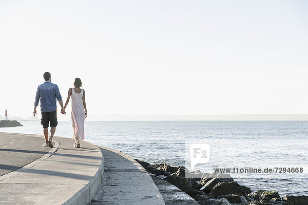 Spain  Mid adult couple walking along coast