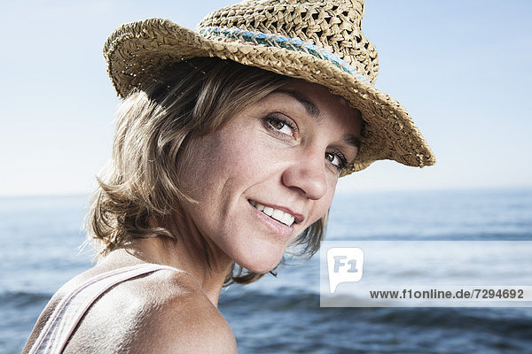 Spain  Mid adult woman with straw hat at Atlantic Ocean  smiling