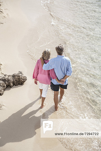 Spain  Seniors couple walking along beach