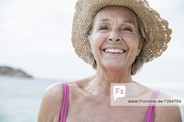 Spain  Senior woman with straw hat on beach