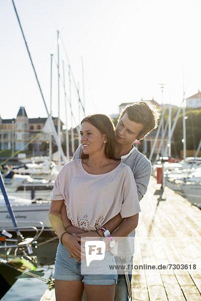 Romantisches junges Paar  das sich auf dem Pier umarmt
