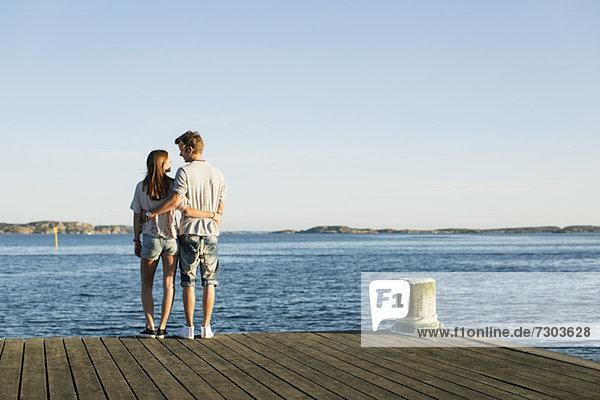 Rückansicht des jungen Paares  das sich umarmt  während es am Pierrand steht.