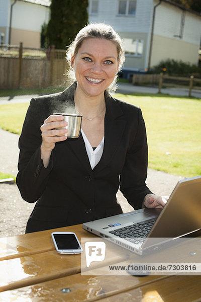 Porträt der glücklichen Geschäftsfrau mit Laptop mit heißer Teetasse
