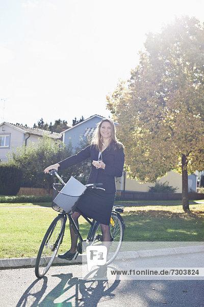Porträt einer glücklichen Geschäftsreisenden mit Fahrrad beim Musikhören