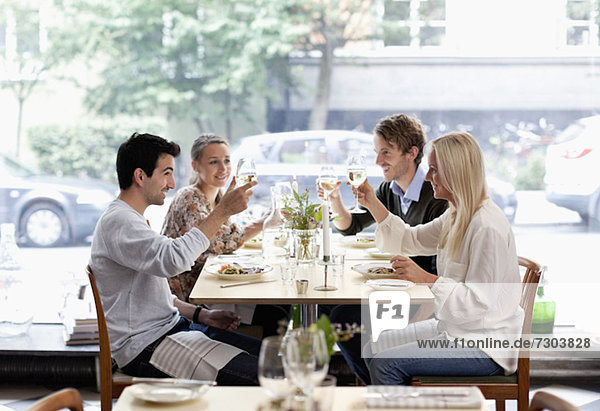 Gruppe von Freunden  die an einem Restauranttisch anstoßen.