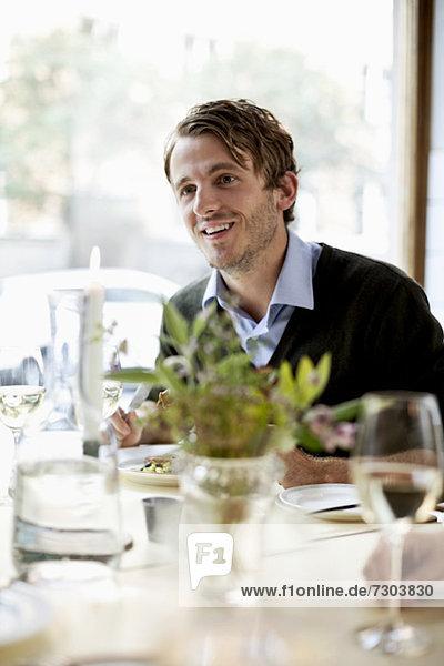 Junger Mann schaut weg zum Restauranttisch