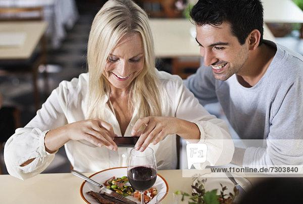 Glückliche Freunde beim Essensfotografieren im Restaurant