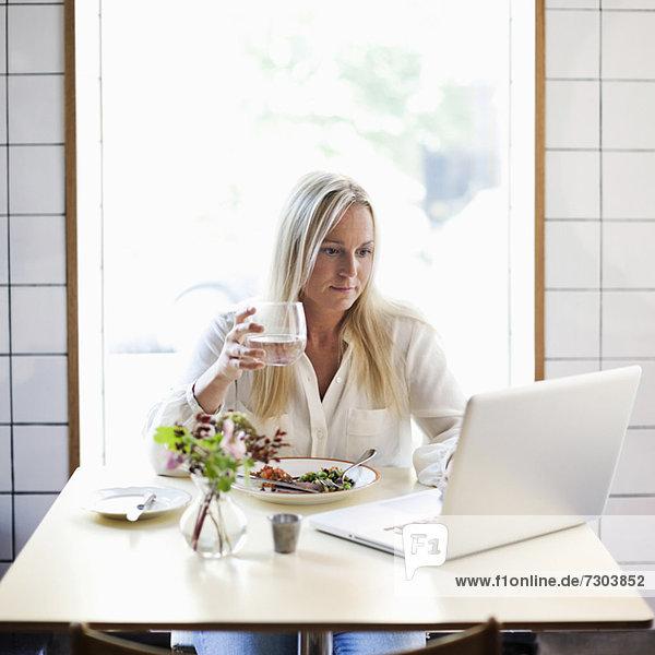 Mittlere erwachsene Frau  die einen Laptop benutzt  während sie ein Glas Wasser am Restauranttisch hält.
