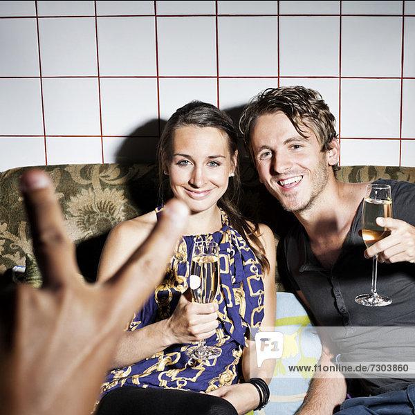 Glückliches Paar schaut auf die Hand des Freundes und gestikuliertes V-Zeichen.