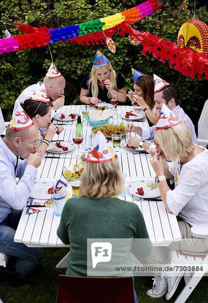 Fröhliche Freunde feiern Krebspartie im Rasen