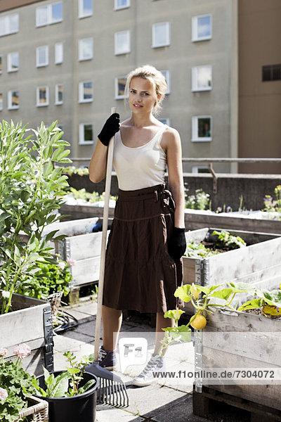 Portrait einer jungen Frau mit Gartengabel am Stadtgarten stehend