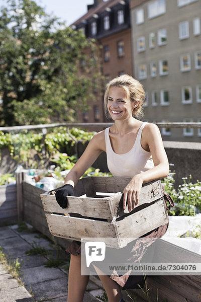 Glückliche junge Frau mit Holzkiste sitzend im Stadtgarten