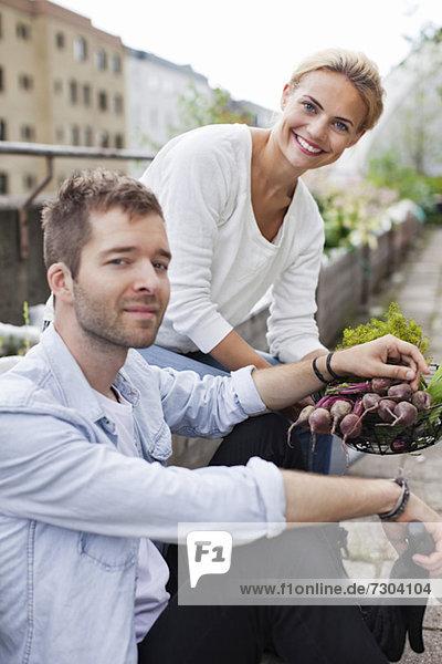 Glückliches junges Paar mit erntefrischem Gemüse im Stadtgarten