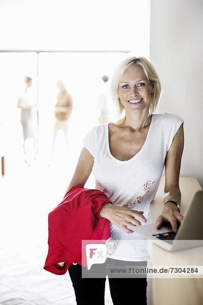 Porträt einer reifen Geschäftsfrau mit Laptop und Kollegen im Büro