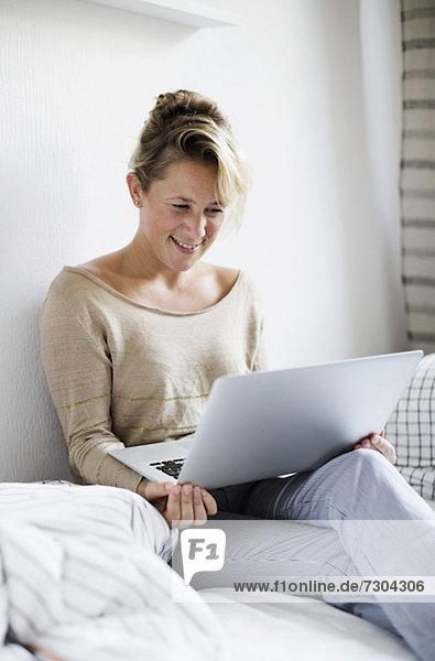 Glückliche Frau mit Laptop im Bett zu Hause