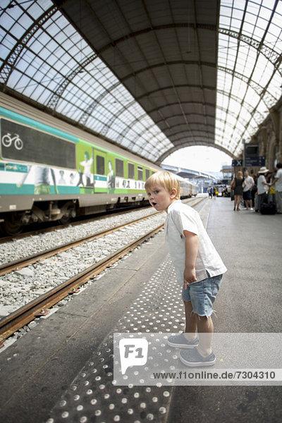Kleiner Junge schaut sich etwas Interessantes auf dem Bahnsteig an.