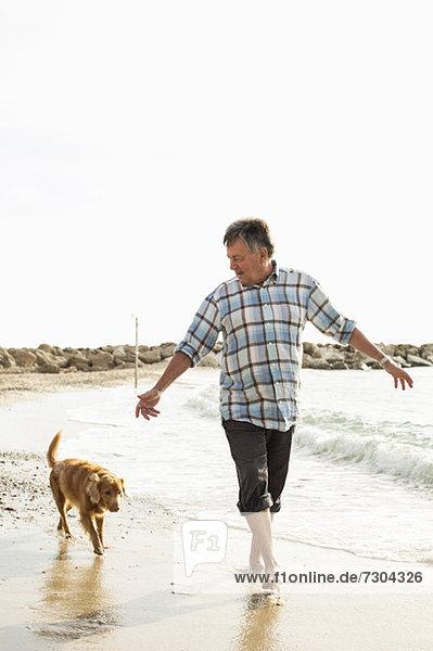 Älterer Mann  der mit Hund am Strand spazieren geht