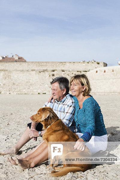 Paar mit Hund auf Sand am Strand sitzend