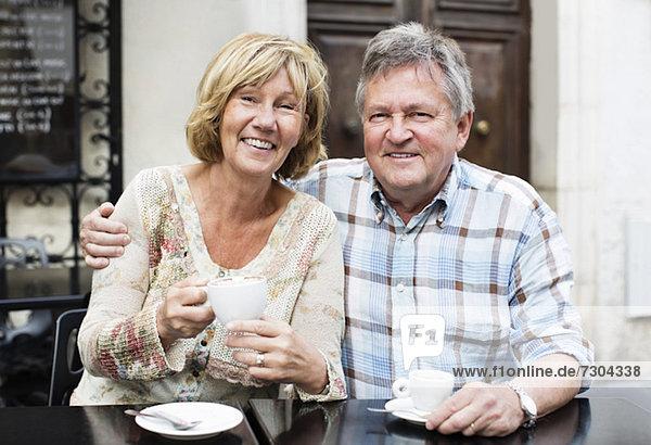 Porträt eines glücklichen Paares beim Kaffee am Tisch