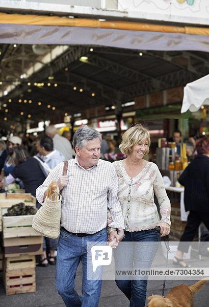 Glückliches Paar mit Hund  der gegen den Markt läuft
