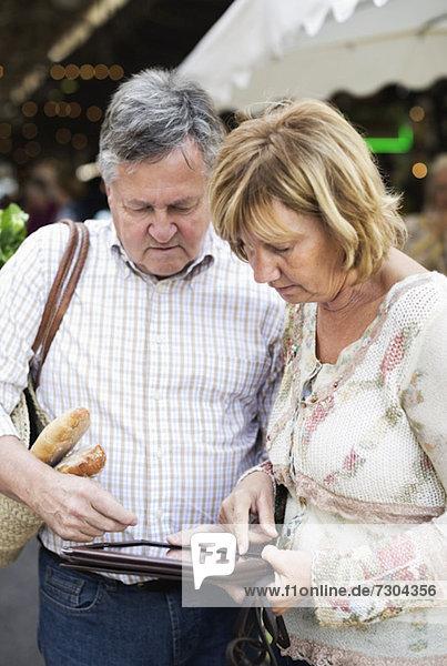Paar mit digitalem Tablett und Markt im Hintergrund