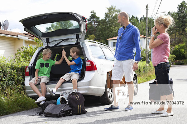 Kaukasisches Paar sieht glückliche Söhne im Kofferraum sitzen  bevor es zum Picknick geht
