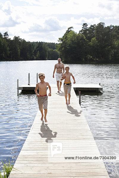 Vorjugendliche Jungen  die auf einer Strandpromenade laufen  während der Vater hinterher läuft.