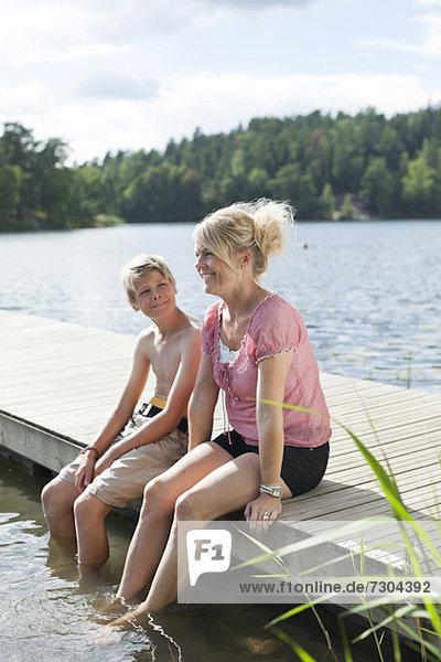 Fröhliche reife Frau sitzend mit Sohn am Pier in den Ferien