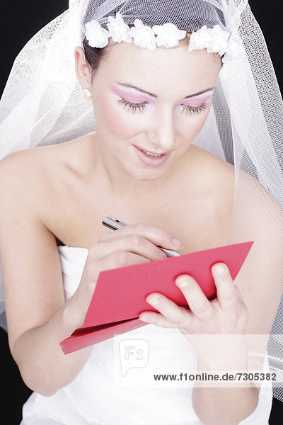 Bride writing on a red paper