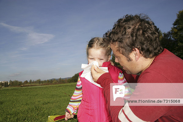 Father blowing his three-year-old daughter's nose