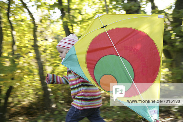 Three-year-old girl playing with kite