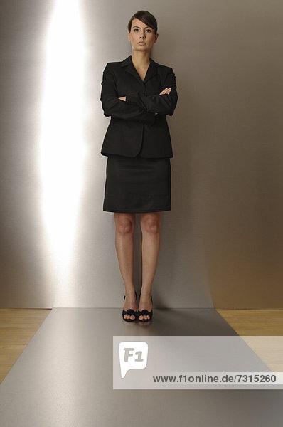 Geschäftsfrau  24 Jahre  steht auf silbernem Boden