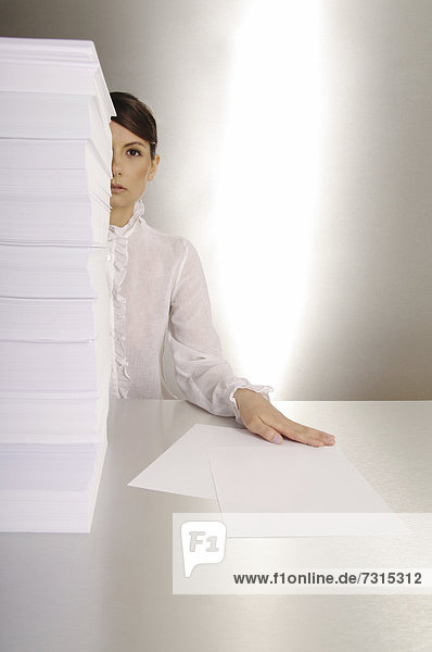 Businesswoman  aged 24  making notes at a silver desktop