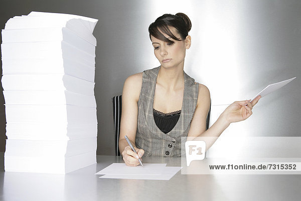 Businesswoman  aged 24  taking notes on a silver desktop