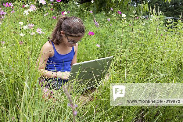 sitzend Computer Notebook arbeiten Wiese Mädchen