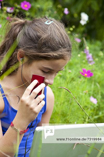 sitzend Computer Notebook Wiese zuhören Mädchen