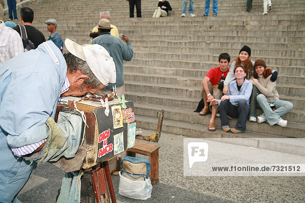 A street photographer photographing tourists with his 106-year-old vintage camera in front of El Capitolio,  national capitol building in Havana,  Cuba,  Caribbean,  Americas