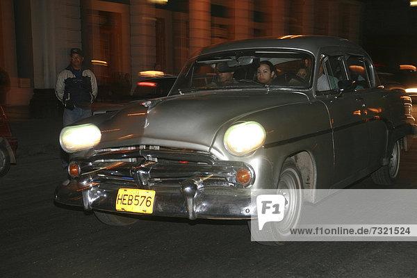 Ein Oldtimer ein privates Taxi fährt nachts in den Straßen von Havanna  Kuba  Amerika