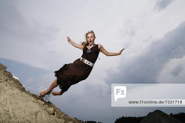 Frau springt von einem Sandhügel